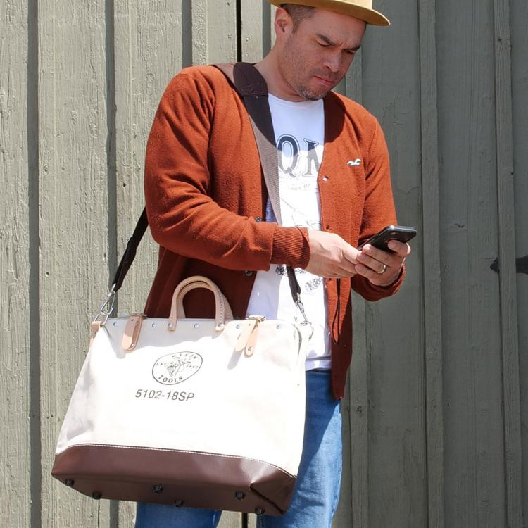 Man carrying white bag holding phone